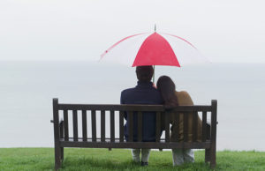 Couple sitting beneath umbrella by ocean